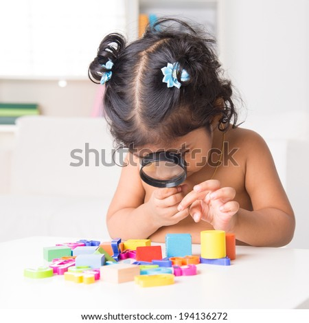A little Indian girl zoom into toys through a magnifying glass, living lifestyle at home. - stock photo