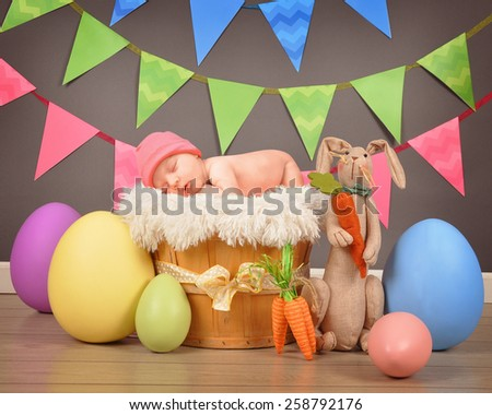 A little newborn baby is sleeping on top of a basket with large Easter eggs and a bunny for a seasonal holiday portrait.