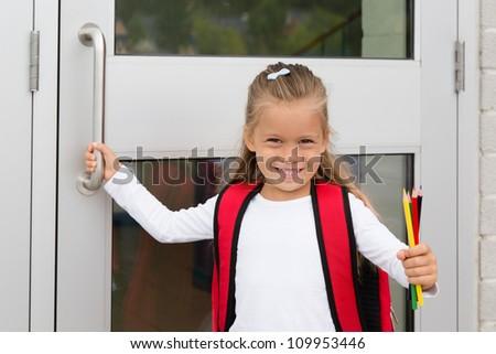 A Little Preteen Schoolgirl Holding a Handle of a School Door Showing her Pencils - stock photo