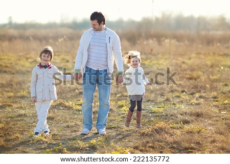 A little pretty girl walking in the field on a cool summer day - stock photo