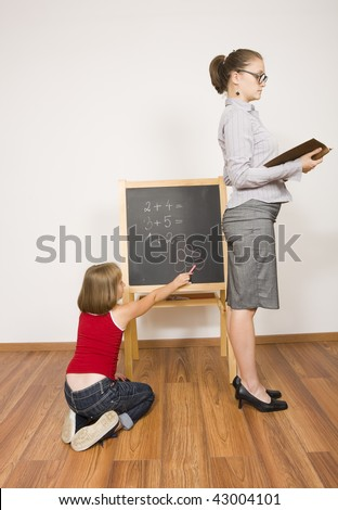 A little schoolgirl drawing a flower, being inattentive in the classroom next to the teacher. - stock photo