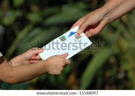 A little white hand of a caucasian girl toddler receiving a letter from her grandmother in the garden during sunset - stock photo