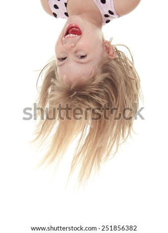 A Little with head upside down in studio - stock photo
