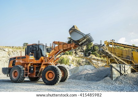 A Loader excavator mining and construction machinery equipment in operating action - stock photo