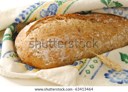A loaf of fresh artisan bread in a basket - stock photo