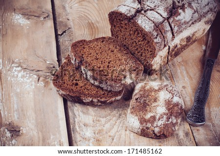 A loaf of fresh rustic wholemeal rye bread, sliced �¢??�¢??on a wooden board, rural food background. - stock photo