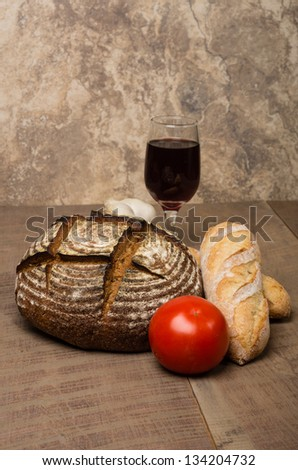 A loaf of fresh rye bread on a table with tomato and a glass of wine