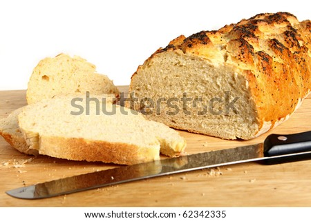 A loaf of homemade bread on a breadboard with a breadknife - stock photo