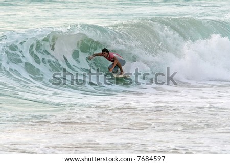 A local surfer tucks into a hollow wave on a beach in Phuket, Thailand