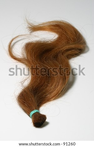 A lock of natural red hair against a white backdrop.  This could symbolize love, or the Irish. - stock photo
