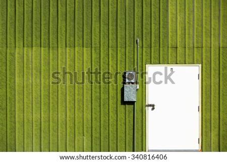 A locked white door on the side of a green sheet metal shed. - stock photo