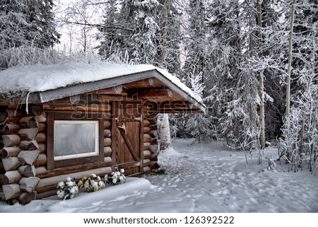 A Log Cabin Frosted Over In Sub Zero Temperatures, With A Trail Leading  Behind It