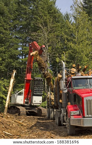 A log loader or forestry machine loads a log truck at the site landing in southern Oregon - stock photo