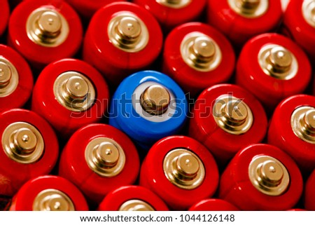 A lone blue AA battery amongst remaining red batteries