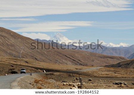 A lone car travels through the barren vastness of rural Tibet.