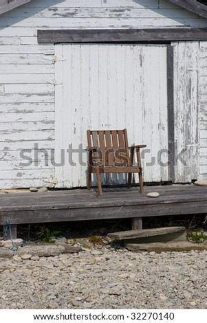 A lone chair outside of a boathouse, where the waterline has not reached for years.  Along the shores of Georgian Bay, in the Bruce Peninsula, Ontario, Canada.