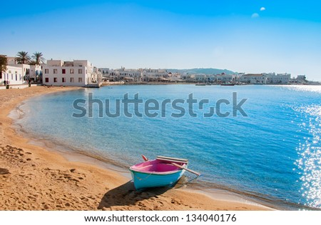 A lone fishing boat on the sand bank on the background of Chora Mykonos and the sky ... Greece. - stock photo