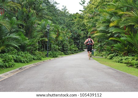 A Lone Jogger At The Singapore Botanic Garden - stock photo