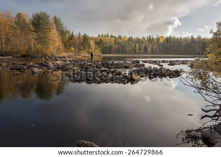 A lone man fishing in the river - stock photo
