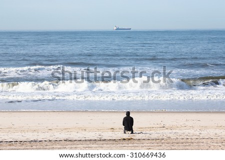 A lone man on sandy beach watching the ocean waves and the ship.