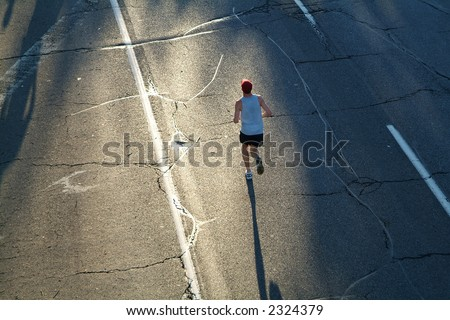 A lone marathon runner heads towards the rising sun during the opening stages of a race. - stock photo