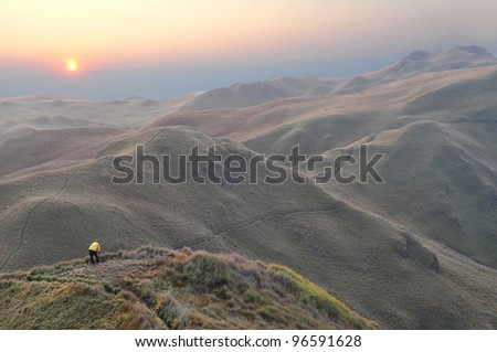 A lone photographer on top of a hill on peaceful mountain ranges. - stock photo