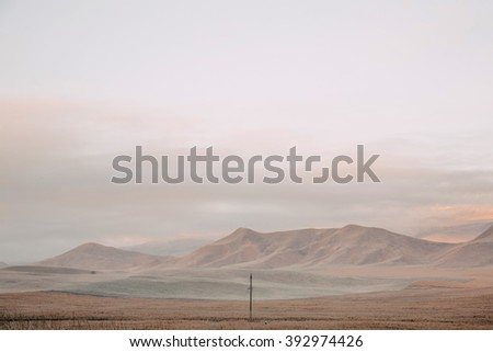 a lone pole in a field on a background of mountains