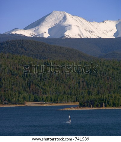 A lone sailboat ventures out while the snow-covered Rockies provide a backdrop - stock photo