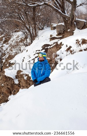 A lone snowboarder examines the slopes - stock photo