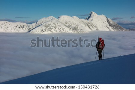 A lone snowshoer pauses to enjoy a wilderness view above the clouds - stock photo