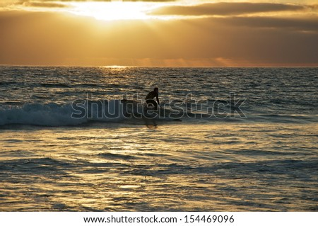 A lone surfer rides a wave at sunset - stock photo