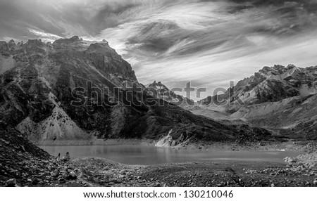A lone tourist near the fifth Gokyo lake ( Ngozumba Tsho ) - Nepal, Himalayas (black and white) - stock photo