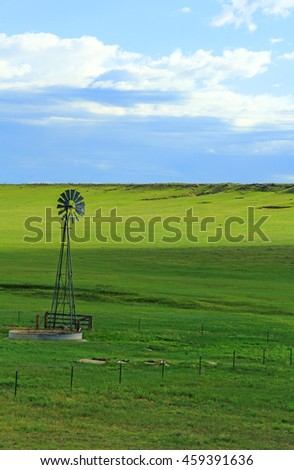 A lonely and serene scene of an old water well on the American prairie. - stock photo