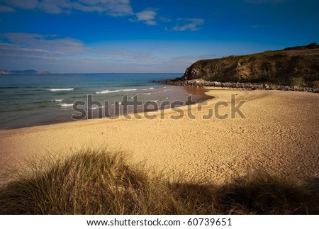 A Lonely beach with a blue sky with few clouds - stock photo