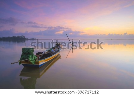 A lonely boat during a beautiful sunrise and nice reflection. Soft focus due to long exposure capture. - stock photo