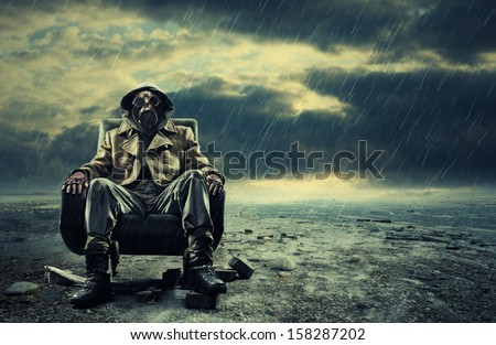 A lonely hero wearing gas mask sitting on armchair - stock photo