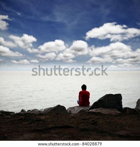 A lonely man in deep thought while sitting on a rocky bank facing the sea with a surreal cloudy blue sky.