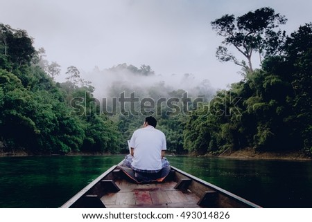 A lonely man sitting on the boat on the beautiful lake during morning. He is watching animals, mainly monkeys in the trees. Ratchaprapha Dam in Khao Sok, Thailand, Asia