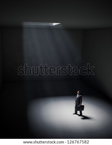 A lonely man standing in a spot of light coming from an opening in the ceiling - stock photo