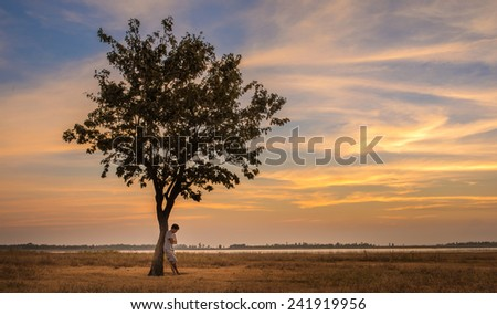 A lonely man thinking of something under the tree - stock photo
