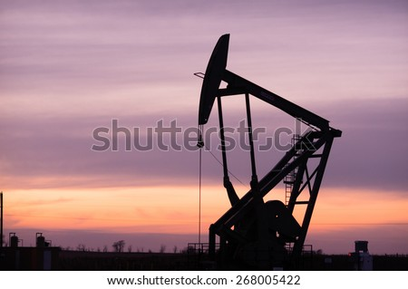 A lonely Pump Jack sits working oil fields at sunset in North Dakota, USA
