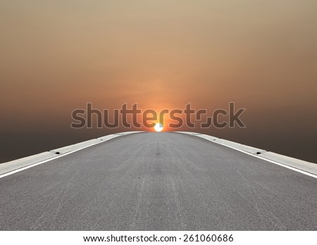 A long asphalt road vanishing into the horizon with a fiery setting sun.  - stock photo