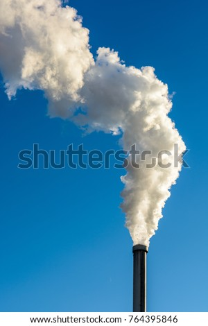 A long cloud of white smoke escaping from a metallic chimney against a deep blue sky.