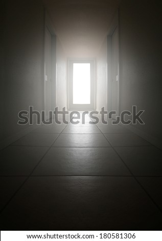 a long dark hallway with light coming from a big window - stock photo
