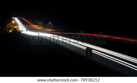 A long exposure at night of headlights and taillights on a busy interstate.
