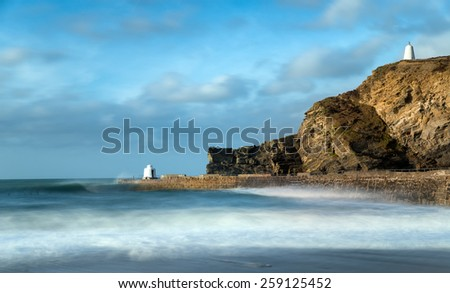 A long exposure of the harbour at Portreath in Cornwall, the white building on the pier is known as the Monkey Hut and the one on the cliffs as the Pepper Pot - stock photo