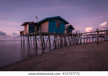 A long exposure shot of houses on stilts by the ocean.