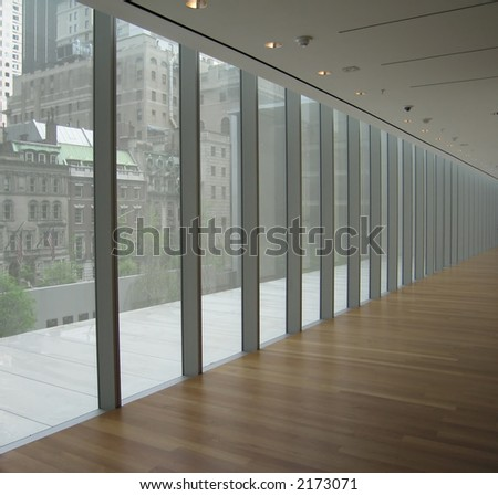 A long glass hallway overlooking the city of New York.