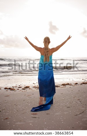 a long haired blonde woman is turned away from the viewer with her arms raised up to the sky as if worshiping the sun - stock photo