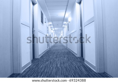 A long hotel corridor perspective with doors. - stock photo